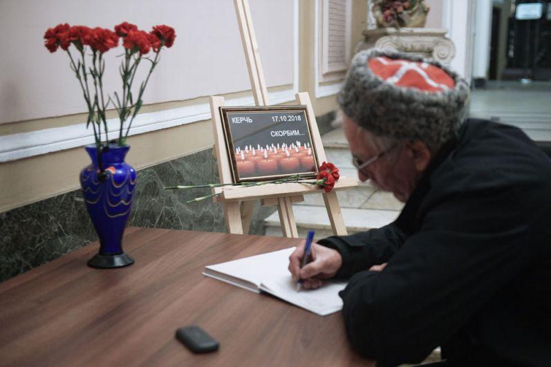 Мужчина оставляет запись в книге соболезнований в Санкт-Петербургском Доме национальностей в связи с происшествием в Керченском политехническом колледже.