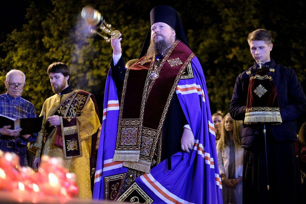 Священнослужитель читает молебен у импровизированного мемориала в Краснодаре в память о погибших при нападении на керченский колледж.