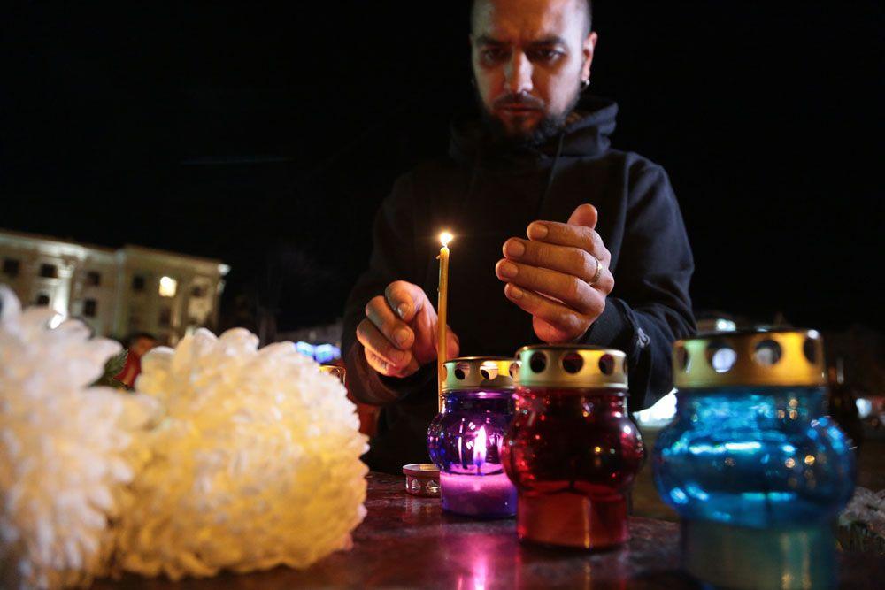 Мужчина зажигает свечу у народного мемориала в Симферополе в память о погибших при нападении на керченский колледж.