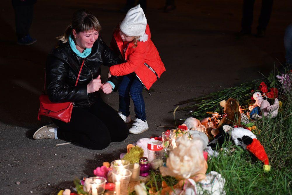 Женщина у народного мемориала на улице в Керчи, где в Керченском политехническом колледже произошли взрыв и стрельба.