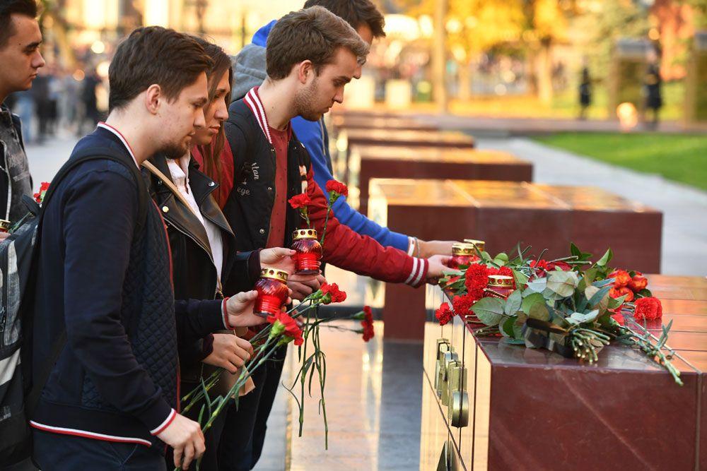 Люди возлагают цветы и ставят свечи на памятник городу-герою Керчи в Александровском саду в Москве в знак траура по погибшим при взрыве в колледже в Керчи.