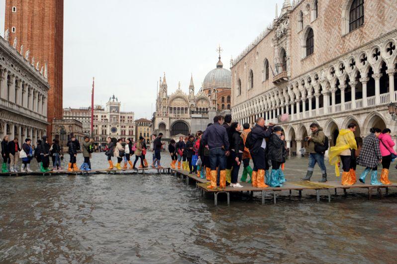 Уровень воды поднялся выше мостков, которые обычно возводят в затопленных районах города, из-за чего их пришлось перестраивать. Туристы и жители передвигаются по улицам в специальных сапогах.