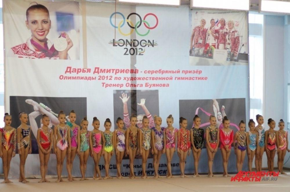 Юные спортсменки выстроились в ряд на открытии соревнований по художественной гимнастике.