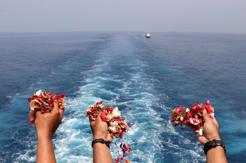 Близкие пассажиров и членов экипажа самолета Lion Air JT610, потерпевшего крушение в Индонезии, бросают цветы в память о погибших на месте катастрофы.
