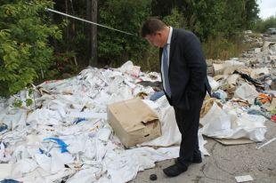 Несанкционированные свалки – головная боль городской власти. Заместитель главы города Сергей Гигирев рассматривает, чей мусор завезли на Сельдинское шоссе.