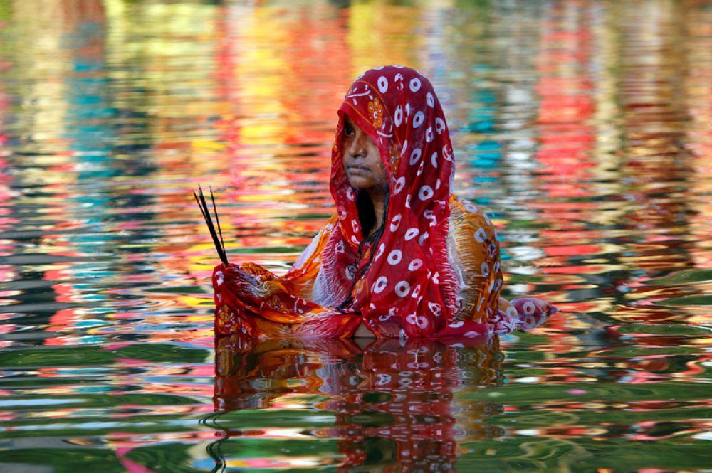 Женщина поклоняется богу Солнца во время религиозного праздника Чхат Пуджа в Агартале, Индия.