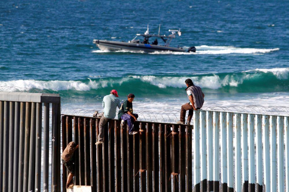 Мексиканские мигранты, пытающихся добраться до США, на вершине пограничной стены между Мексикой и Соединенными Штатами, Тихуана.
