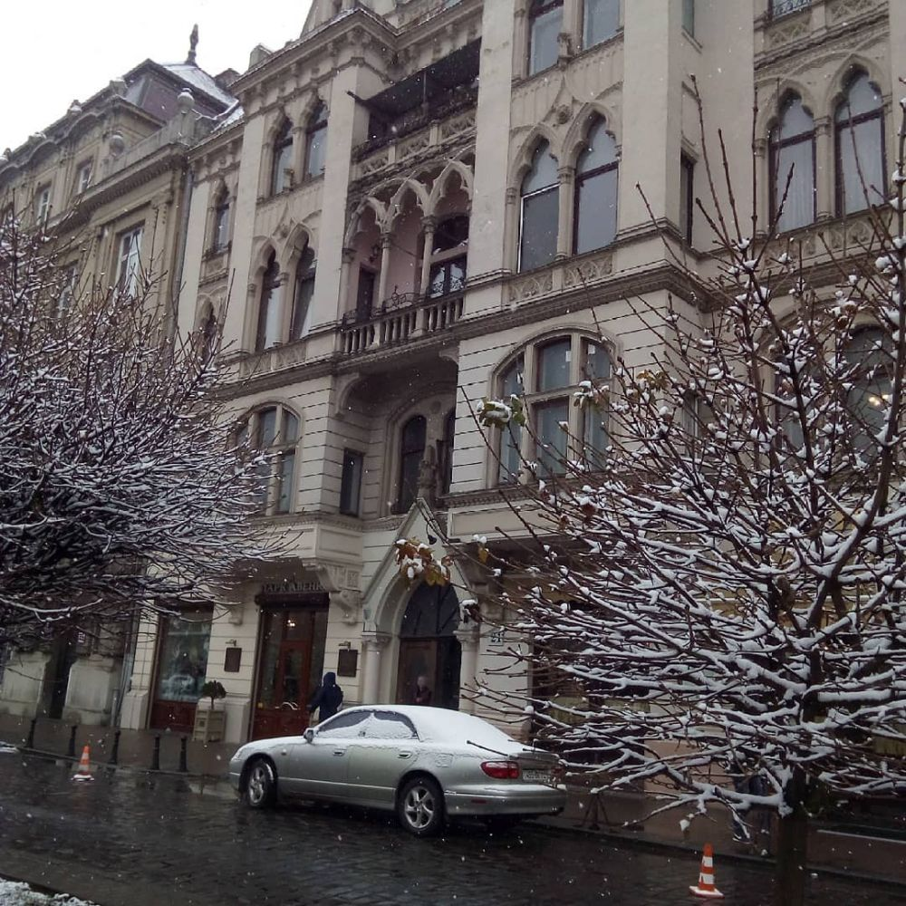 Город превратился в настоящую зимнюю сказку. Деревья, машины, дороги - все в снегу.