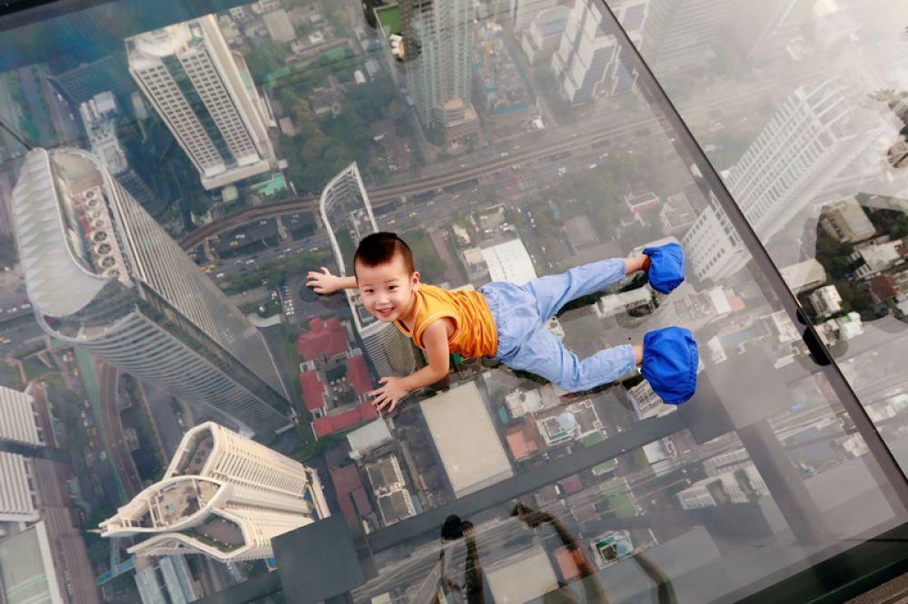 Мальчик на смотровой площадке, открывшейся на вершине небоскреба King Power Mahanakhon в Бангкоке. Площадка со стеклянным полом расположена на высоте 314 метров, откуда открывается 360-градусный вид на город.