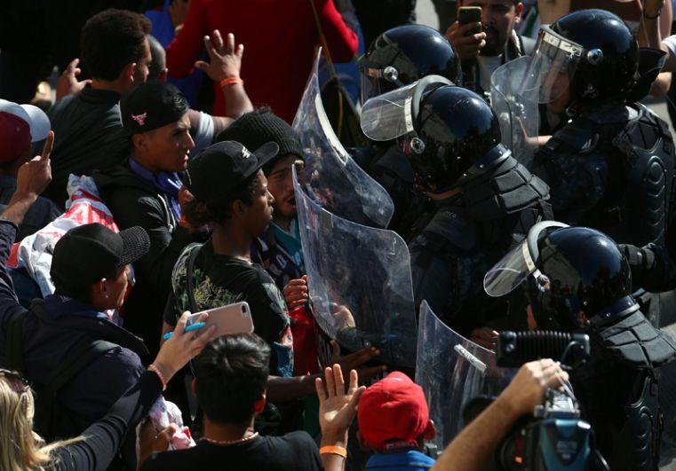 Мигранты и останавливающие их бойцы ОМОН на границе между Мексикой и Соединенными Штатами в Тихуане.