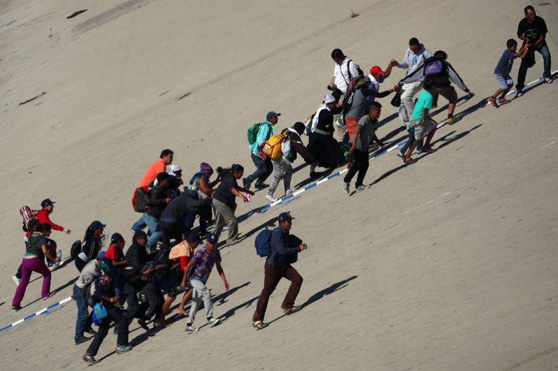 Мигранты возвращаются на мексиканскую сторону после попытки незаконного пересечения границы в Тихуане.