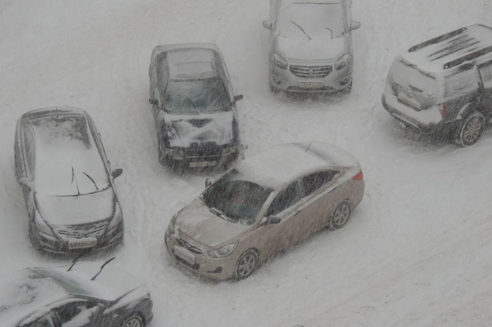 Транспорт на парковках заносит снегом.