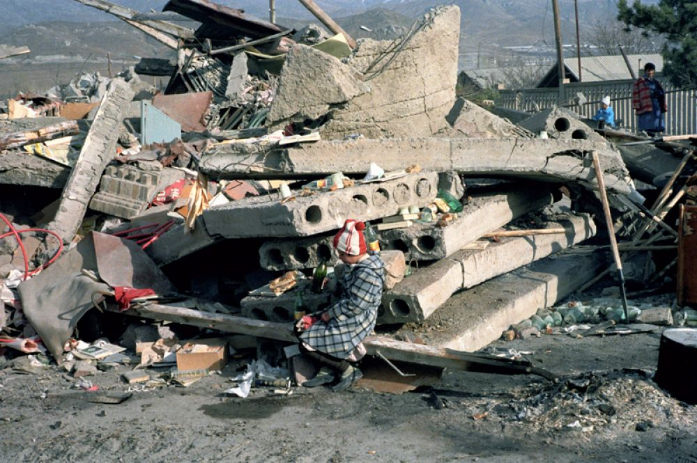 Ребенок на развалинах родного дома, разрушенного в результате землетрясения.
