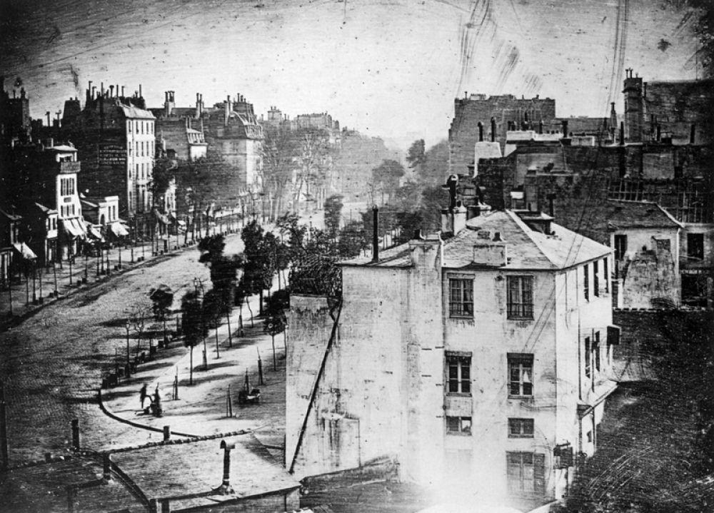 Самое раннее дагеротипное изображение человека, сделанное Дагером. Вид на бульвар дю Тампль в Париже весной 1838 года. В левом нижнем углу видны чистильщик обуви и его клиент. Все движущиеся фигуры и экипажи из-за длинной выдержки не отобразились на снимке.