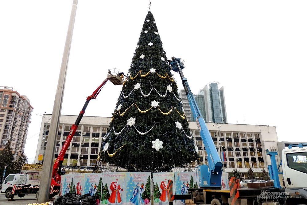 Рабочие украшают главную ёлку Краснодара с помощью подъёмников.