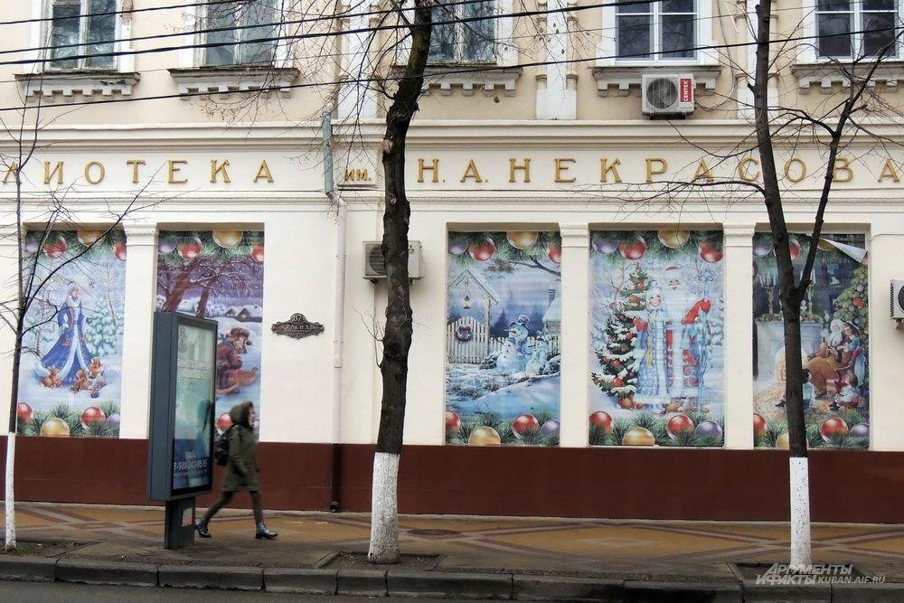 Окна городской библиотеки имени Некрасова украсили праздничными баннерами.