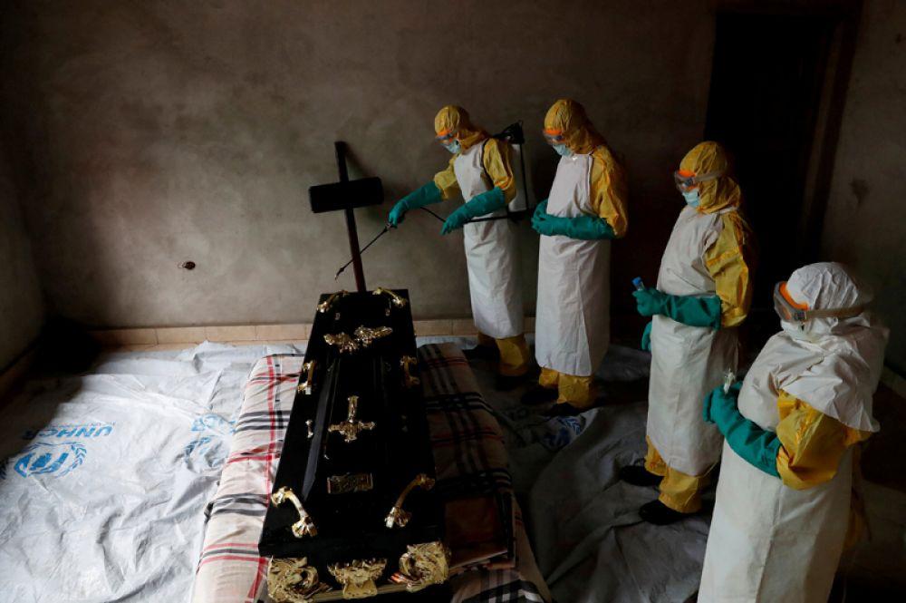 Медицинский работник опрыскивает комнату во время похорон человека, умершего от лихорадки Эбола, в Бени, Республика Конго.