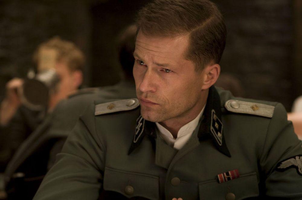 «Бесславные ублюдки» (2009). Швайгеру досталась роль сержанта Хуго Штиглица, убившего нескольких офицеров гестапо, ожидающего трибунала и освобожденного «Ублюдками».
