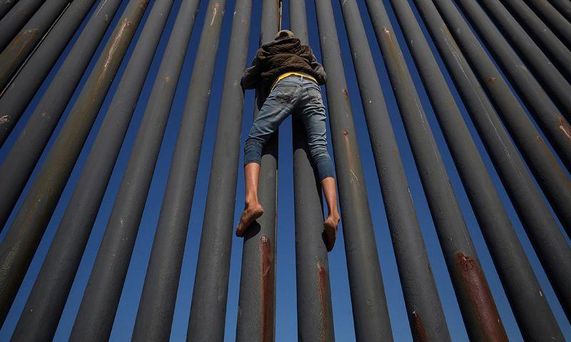 Участник каравана мигрантов из Центральной Америки пытается перелезть через пограничный забор между Мексикой и Соединенными Штатами в Тихуане, 18 ноября 2018 года.