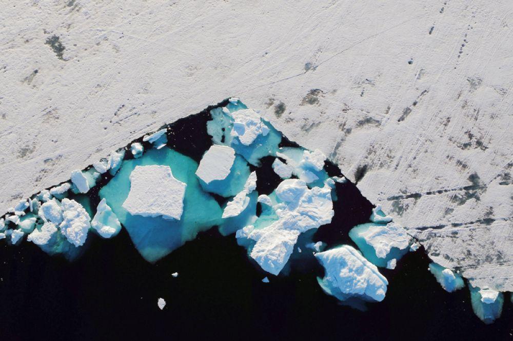 Таяние айсберга во фьорде недалеко от города Тасиилак, Гренландия, 18 июня 2018 года.