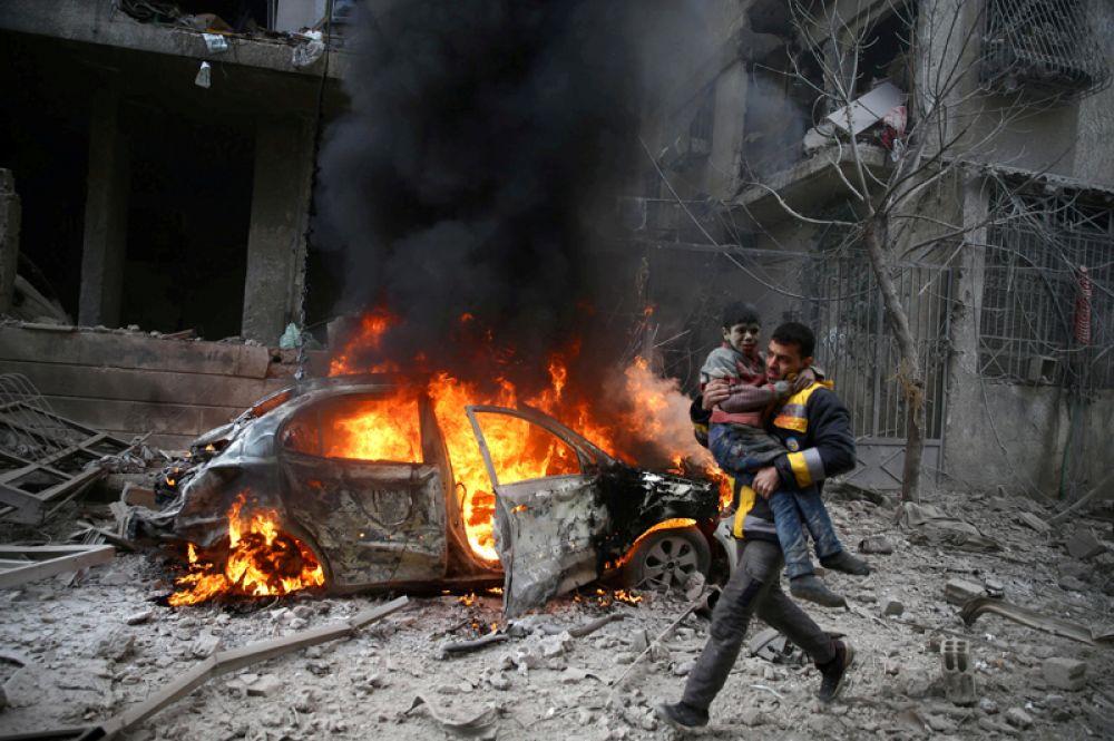 Доброволец «Сирийской гражданской обороны» спасает раненного ребенка из осажденного города Хамория, Восточная Гута, Дамаск, Сирия, 6 января 2018 года.