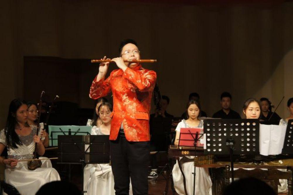 Студент вуза играет в местном оркестре народных инструментов.