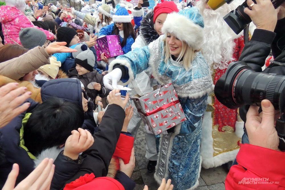 Снегурочка раздаёт подарки детям.
