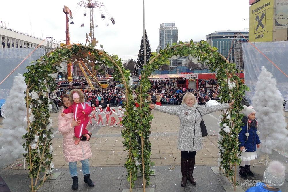 Зрители фотографируются на фоне праздничных декораций.