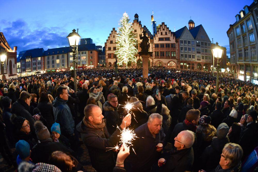 Тысячи людей собрались в канун Рождества на площади Франкфурта-на-Майне, чтобы послушать колокольный концерт.