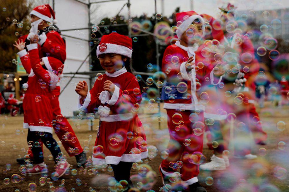Дети в костюмах Санта-Клауса в Токио, Япония.
