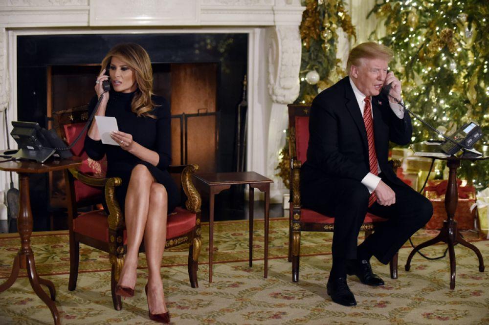 Дональд и Мелания Трамп отвечают на звонки детей в рамках программы NORAD Tracks Santa, которая сообщает вымышленный путь Санта-Клауса, покинувшего Северный полюс и отправившегося разносить подарки детям по всему миру.