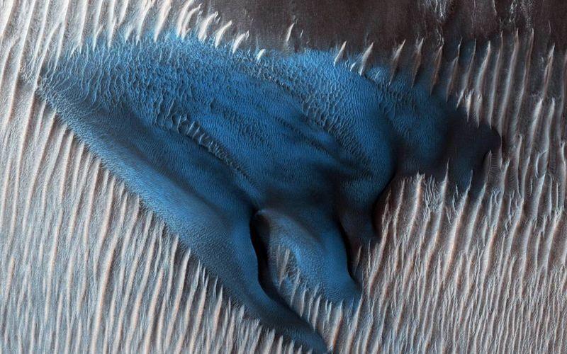 Голубые дюны на Марсе. По словам специалистов, такие явления нередко можно наблюдать на поверхности кратеров, но, как правило, они серого цвета. Исследователи объясняют яркий цвет дюн их более сложной структурой и особым химическим составом.