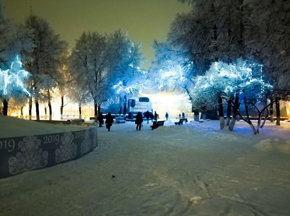 Парк рядом с фонтаном украсили разноцветными гирляндами. Природа тоже не осталась в стороне и помогла в создании атмосферы праздника – на деревьях красивый белый иней. Поэтому прямо с автобусной остановки мы попадаем в сказочный лес.