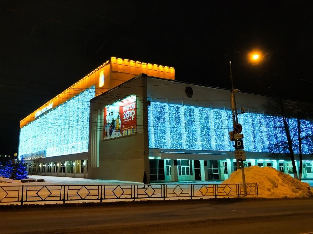 Здание украшено тысячами маленьких огоньков, что выглядит грандиозно на фоне серых зданий, находящих поблизости.
