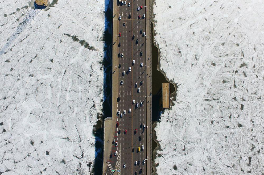 Машины проезжают по мосту через замерзшую реку Хун в Шеньяне, Китай.