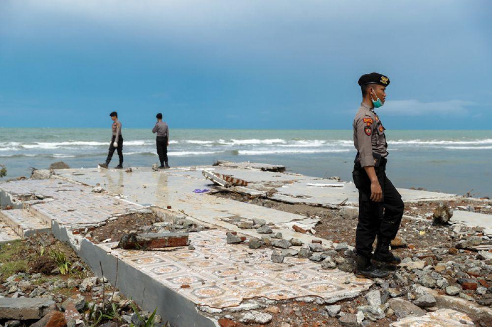 Полицейские разыскивают жертв среди обломков разрушенного прибрежного отеля, пострадавшего от цунами в Пандегланге, Индонезия.