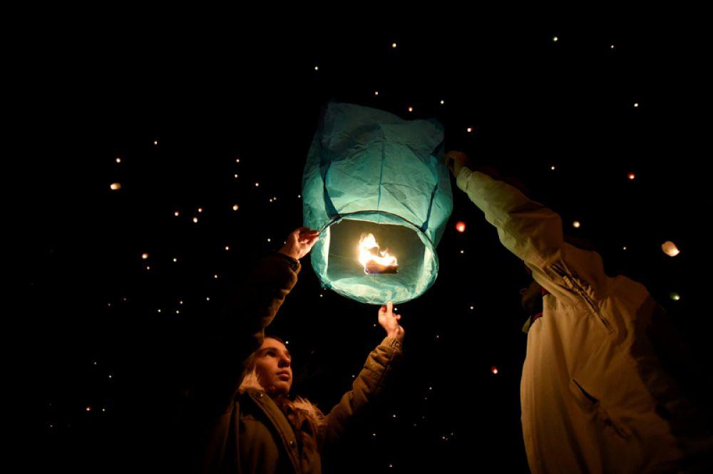 Люди запускают небесные фонарики во время рождественских гуляний в Волосе, Греция.