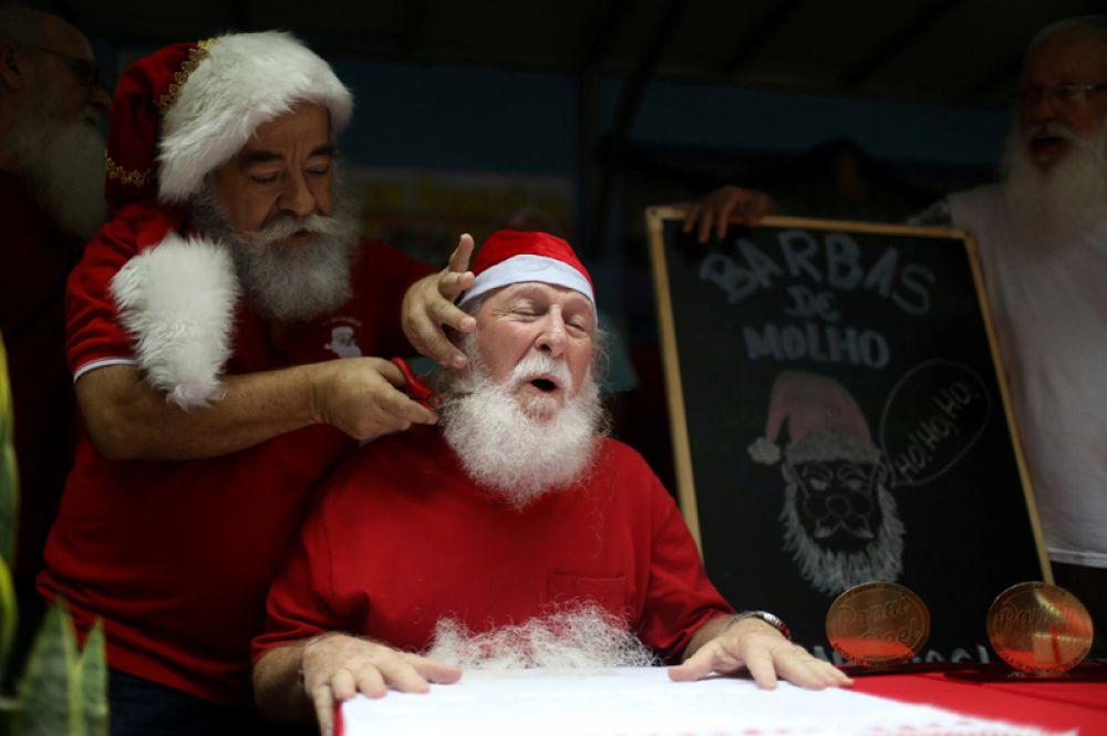 Ученику бразильской школы Санта-Клаусов остригают бороду в честь окончания рождественского сезона в Рио-де-Жанейро.