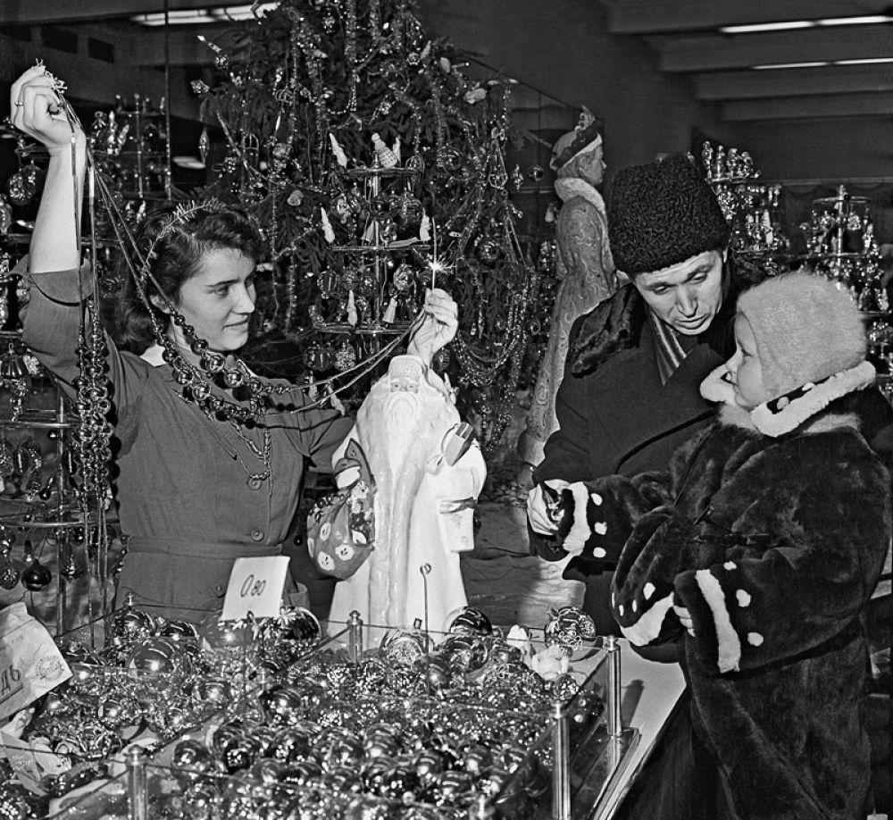 Папа с маленькой дочкой выбирают елочные украшения в магазине «Детский мир» в Москве. 1958 год.