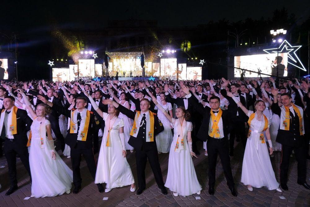 Губернаторский бал выпускников. На фото: юноши и девушки вальсируют на площади перед зданием Законодательного собрания края.