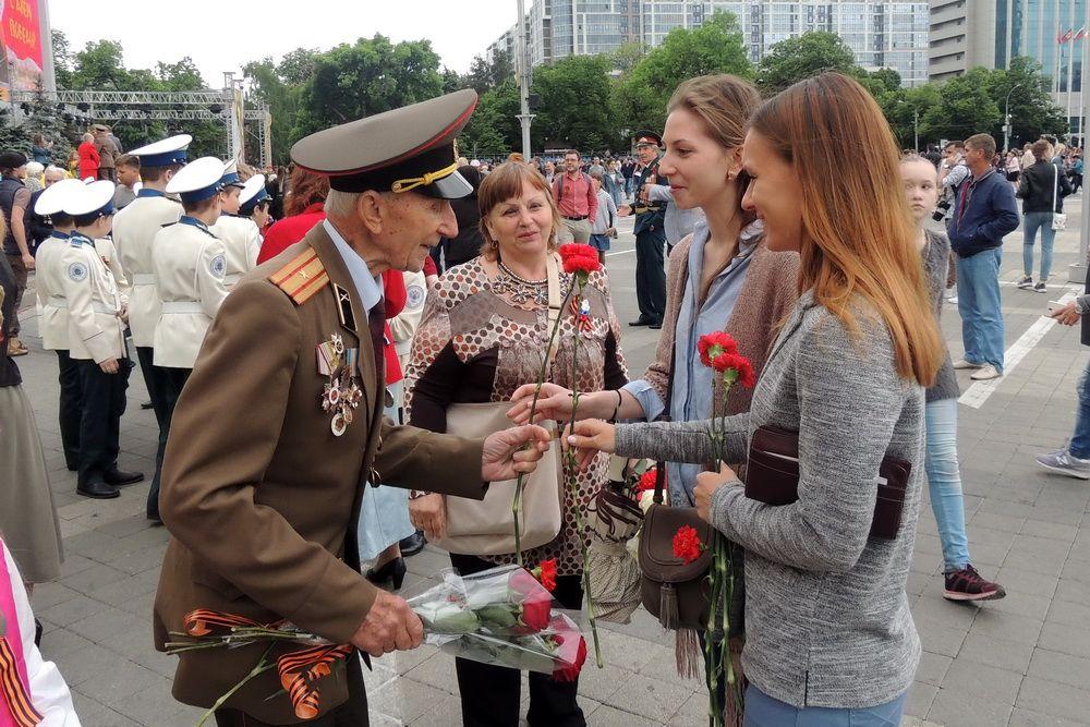 На Кубани отметили 73-ю годовщину Победы. На фото: девушки вручают цветы ветерану 9 мая 2018 года в Краснодаре.