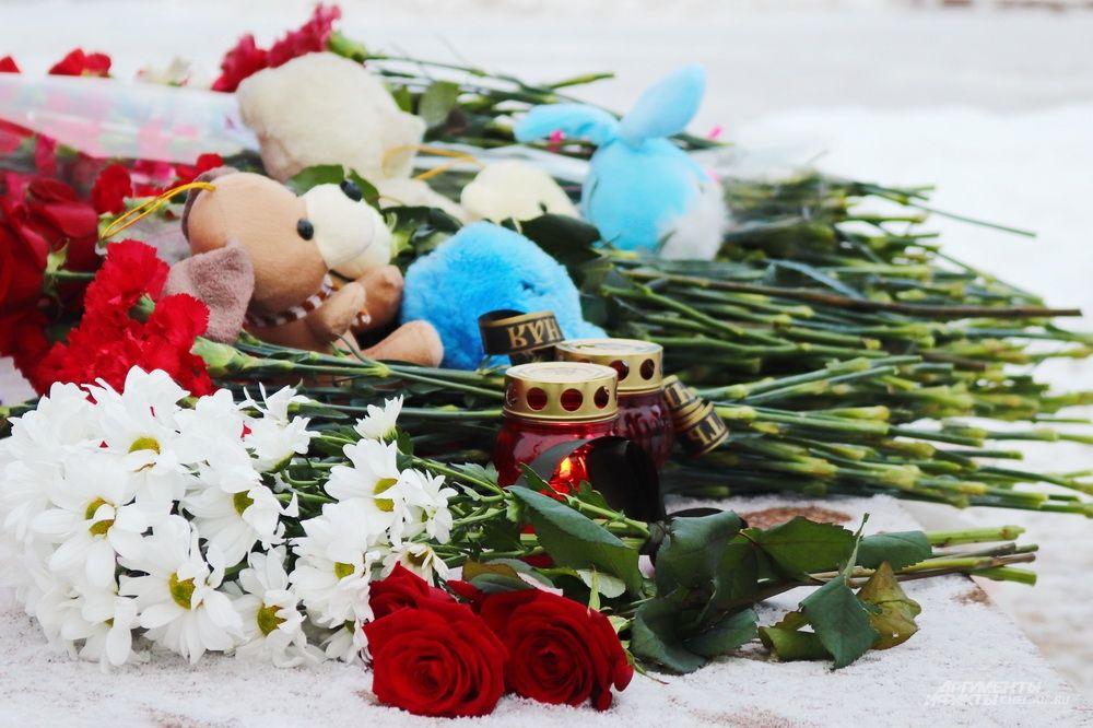 Вместе с цветами горожане несли игрушки - среди погибших есть несколько детей.