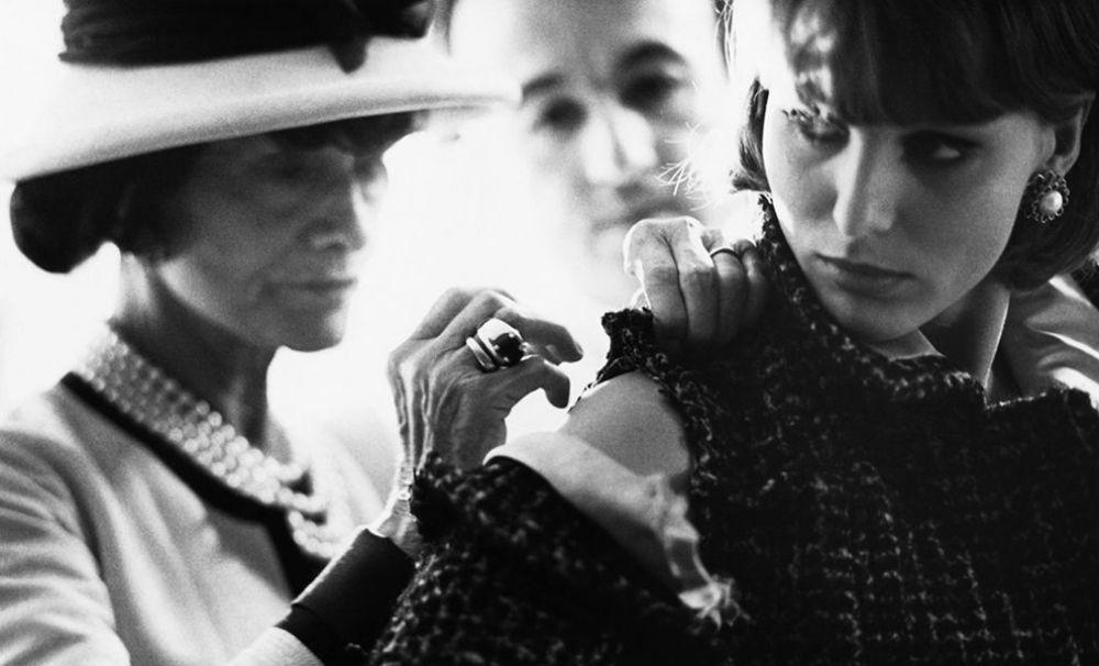 """Коко Шанель за работой. """"Женщина должна одеваться так, чтобы ее было приятно раздевать"""" - этим высказыванием и стоит озаглавить послевоенный период творчества Коко Шанель. Из-под ее легкой руки выходят шифоновые платья и женственные шляпы с вуалью, в небытие уходит сигарета и все чаще темные цвета уступают белому в коллекциях. 1960-ые - это время славы духов Chanel №5. """"Духи говорят о женщине больше, чем её почерк"""" - говорила Шанель."""