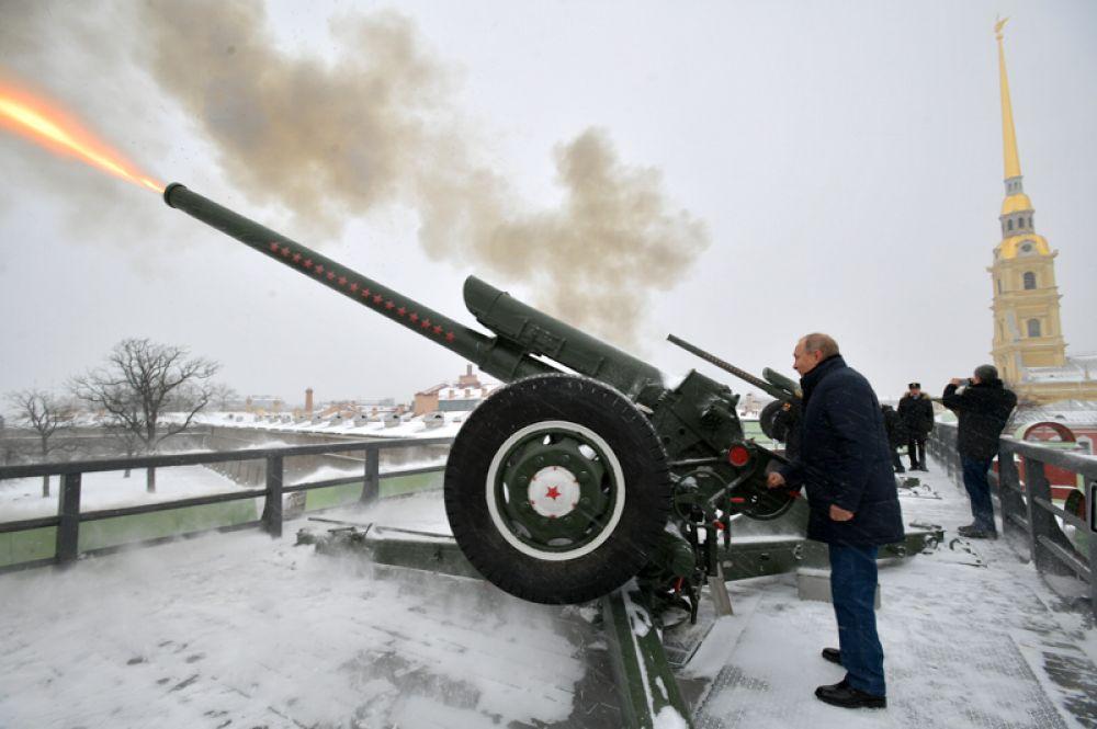 Президент РФ Владимир Путин производит традиционный полуденный выстрел из пушки во время прогулки по Петропавловской крепости.