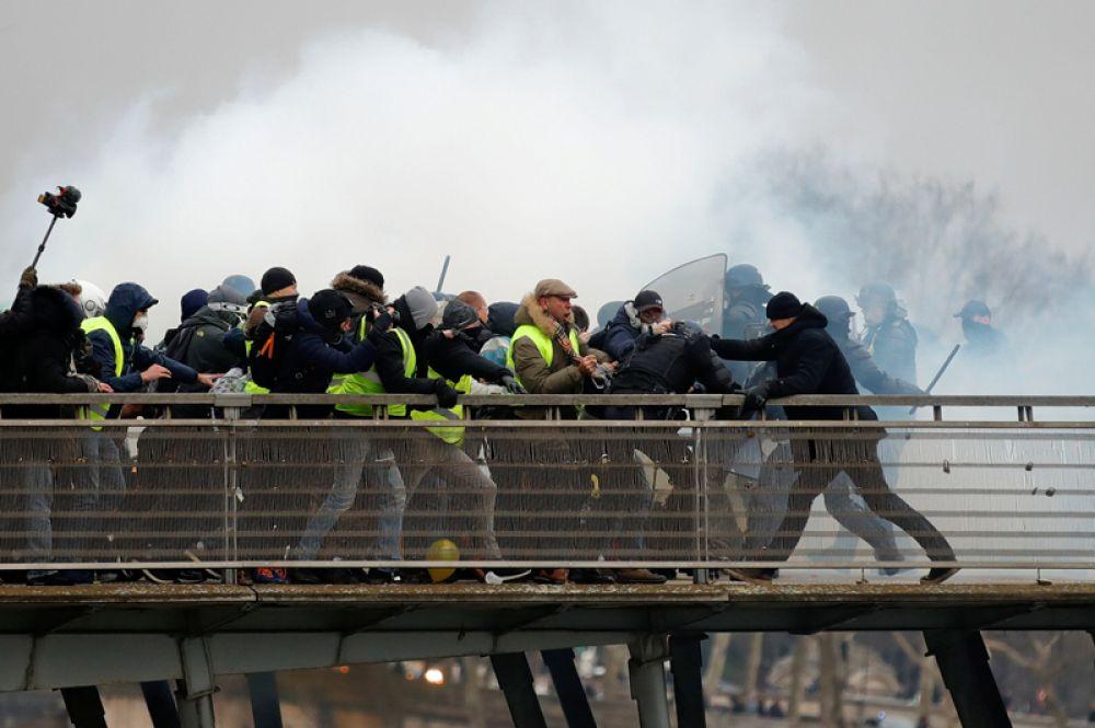 Столкновение участников демонстрации «желтых жилетов» с французскими жандармами на мосту Леопольда Седара Сенгора в Париже.