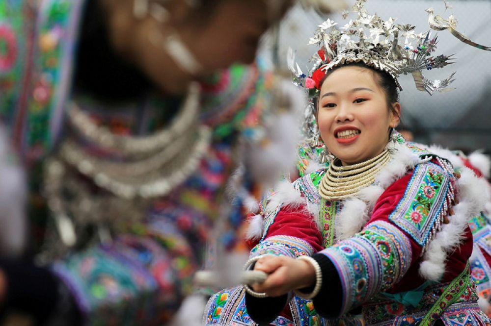 Женщины народа мяо в традиционных костюмах принимают участие в перетягивании каната на праздновании Нового года, Китай.