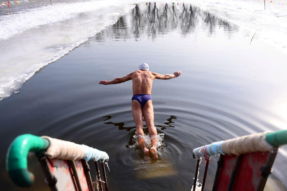 Пловец ныряет в ледяной водоем в парке в Шеньяне, Китай.