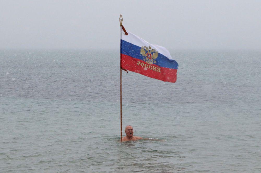 Любитель зимнего плавания во время праздничного мероприятия, посвященного православному Рождеству, в черноморском порту Евпатория, Крым.
