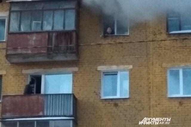 Женщина в окне просит помощи.