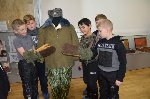 Юные курьинцы примеряют рукавицы, в которых Калашников ходил на зимнюю охоту.